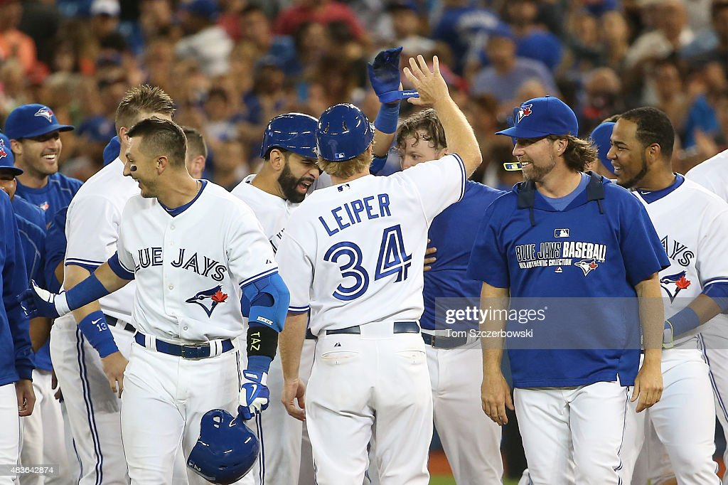 Josh Donaldson #20 of the Toronto Blue Jays is congratulated by Jose Bautista #19 and first base coach Tim Leiper #34 after his game-winning RBI single in the eleventh inning during MLB game action against the Kansas City Royals on July 31, 2015 at Rogers Centre in Toronto, Ontario, Canada.