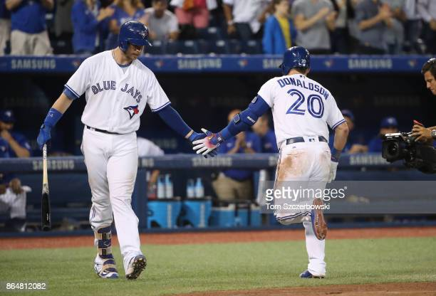 Josh Donaldson of the Toronto Blue Jays is congratulated by Justin Smoak after hitting a solo home run in the fifth inning during MLB game action...