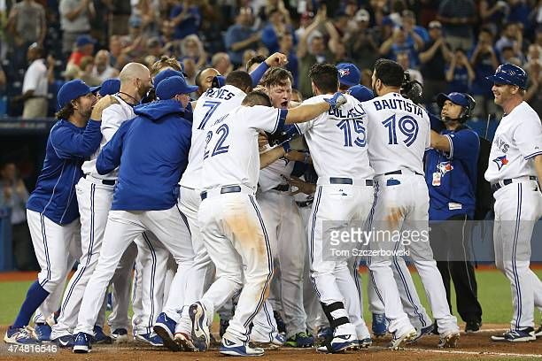 Josh Donaldson of the Toronto Blue Jays is congratulated by teammates on his gamewinning threerun home run in the ninth inning during MLB game action...
