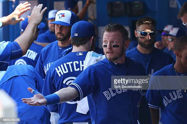 Josh Donaldson of the Toronto Blue Jays is congratulated by teammates after driving in and scoring a run in the third inning during MLB game action...