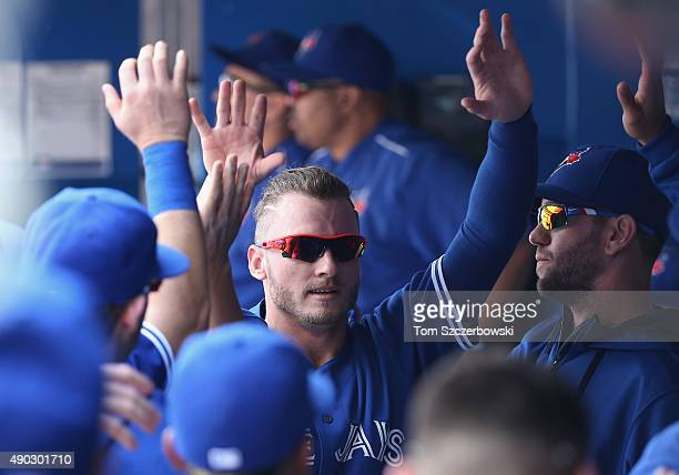 Josh Donaldson of the Toronto Blue Jays is congratulated by teammates in the dugout after scoring a run in the first inning during MLB game action...