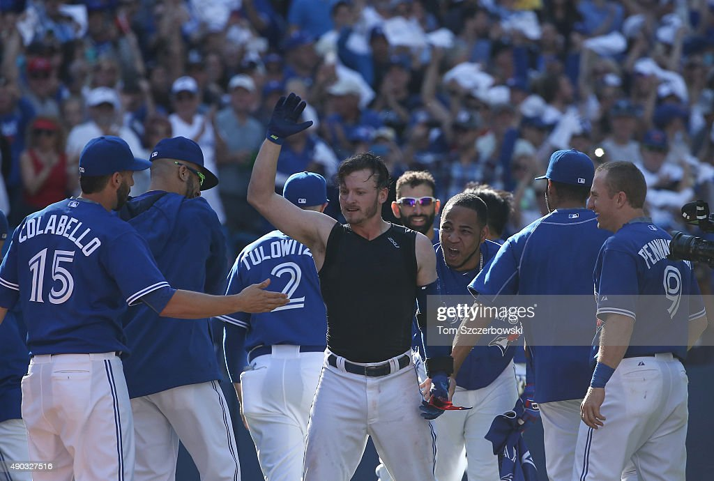 Josh Donaldson #20 of the Toronto Blue Jays is congratulated by teammates at home plate after hitting a game-winning solo home run in the ninth inning during MLB game action against the Tampa Bay Rays on September 27, 2015 at Rogers Centre in Toronto, Ontario, Canada.