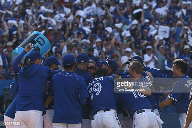 Josh Donaldson of the Toronto Blue Jays is congratulated by teammates at home plate after hitting a gamewinning solo home run in the ninth inning...