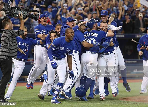 Josh Donaldson of the Toronto Blue Jays is congratulated by teammates after scoring the gamewinning run in the tenth inning during MLB game action...