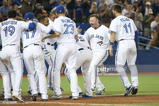 Josh Donaldson of the Toronto Blue Jays is congratulated on his gamewinning threerun home run in the ninth inning during MLB game action against the...