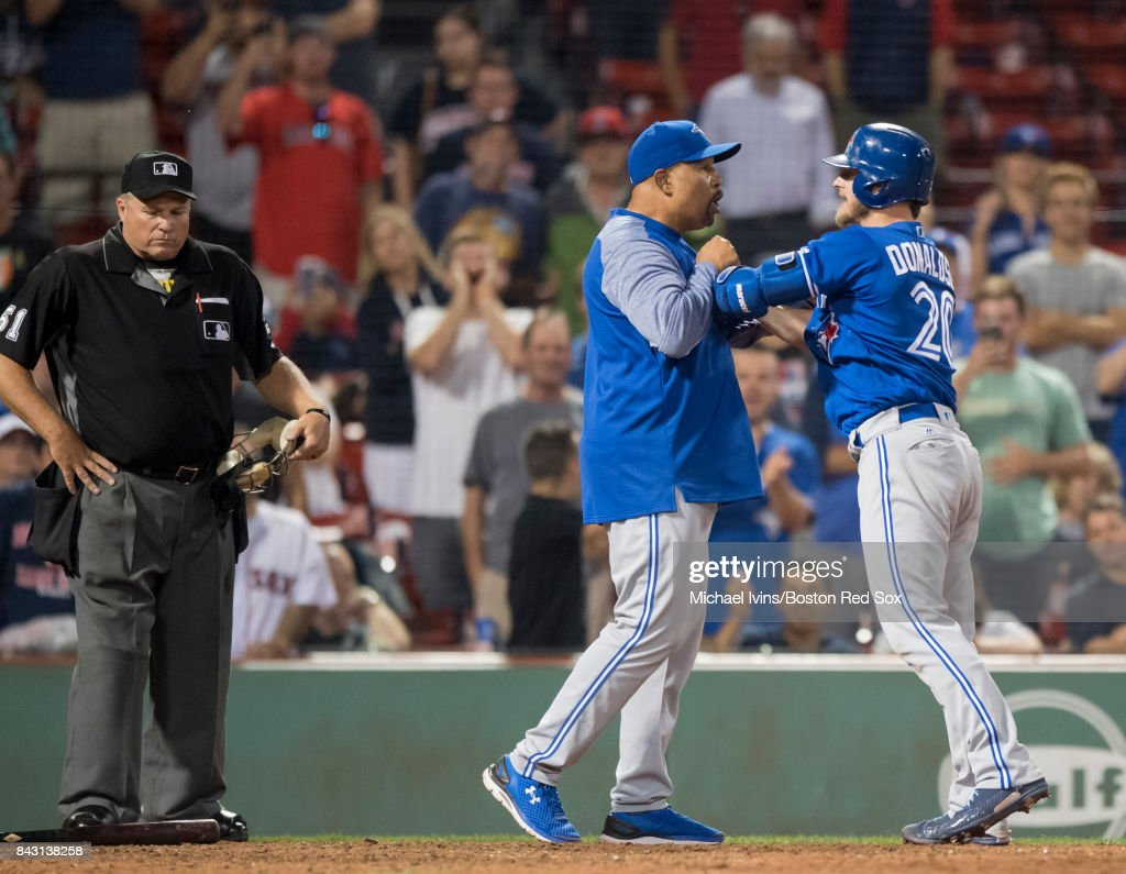 Josh Donaldson #20 of the Toronto Blue Jays is restrained by bench coach DeMarlo Hale #16 after being ejected from a game against the Boston Red Sox for arguing a strike call with home plate umpire Marvin Hudson #51 in the 18th inning at Fenway Park on September 5, 2017 in Boston, Massachusetts.