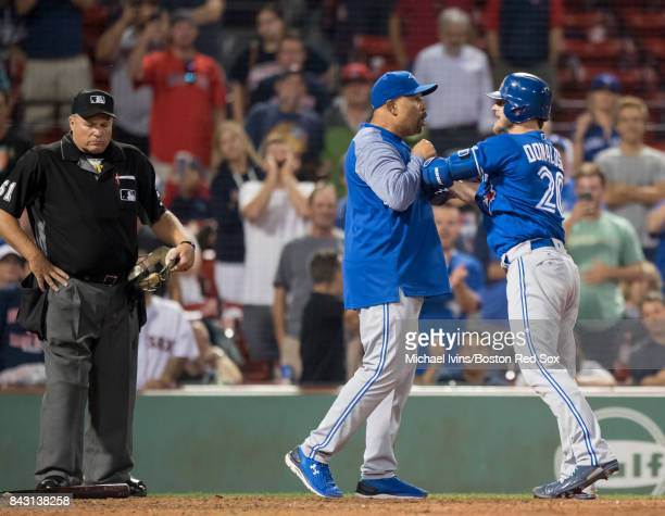 Josh Donaldson of the Toronto Blue Jays is restrained by bench coach DeMarlo Hale after being ejected from a game against the Boston Red Sox for...