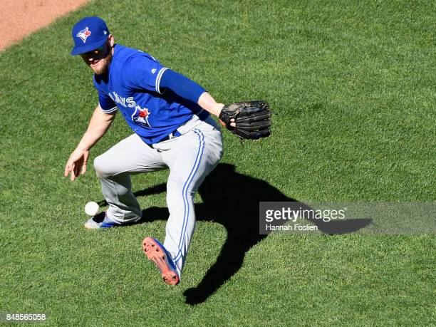 Josh Donaldson of the Toronto Blue Jays is unable to field a bunt single by Brian Dozier of the Minnesota Twins during the fifth inning of the game...
