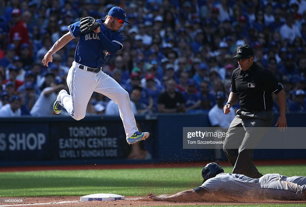 Josh Donaldson #20 of the Toronto Blue Jays jumps for a high throw as Mikie Mahtook #27 of the Tampa Bay Rays steals third base in the eighth inning during MLB game action on September 27, 2015 at Rogers Centre in Toronto, Ontario, Canada.