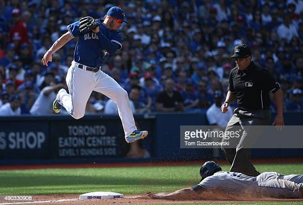 Josh Donaldson of the Toronto Blue Jays jumps for a high throw as Mikie Mahtook of the Tampa Bay Rays steals third base in the eighth inning during...
