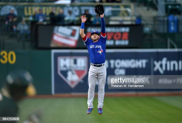 Josh Donaldson of the Toronto Blue Jays leaps for a line drive hit over his head off the bat of Rajai Davis of the Oakland Athletics in the bottom of...