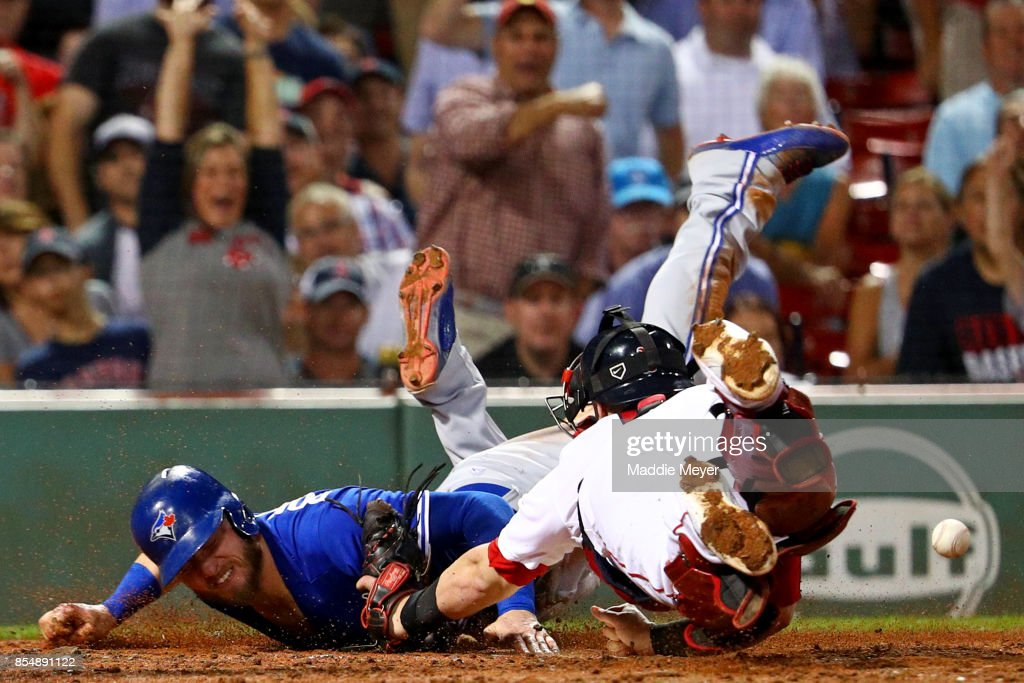 Josh Donaldson #20 of the Toronto Blue Jays slides past Christian Vazquez #7 of the Boston Red Sox to score a run during the third inning at Fenway Park on September 27, 2017 in Boston, Massachusetts.