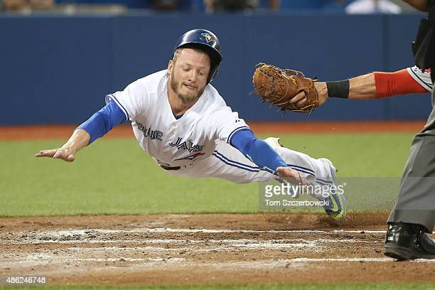 Josh Donaldson of the Toronto Blue Jays slides safely across home plate to score on a sacrifice fly in the second inning during MLB game action as...