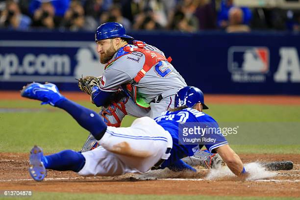 Josh Donaldson of the Toronto Blue Jays slides safely into home plate past Jonathan Lucroy of the Texas Rangers in the tenth inning for the Toronto...