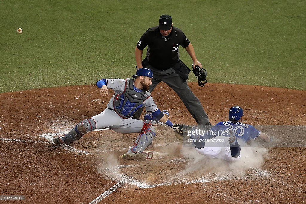 Josh Donaldson #20 of the Toronto Blue Jays slides safely into home plate past Jonathan Lucroy #25 of the Texas Rangers in the tenth inning for the Toronto Blue Jays to defeat the Texas Rangers 7-6 for game three of the American League Division Series at Rogers Centre on October 9, 2016 in Toronto, Canada.