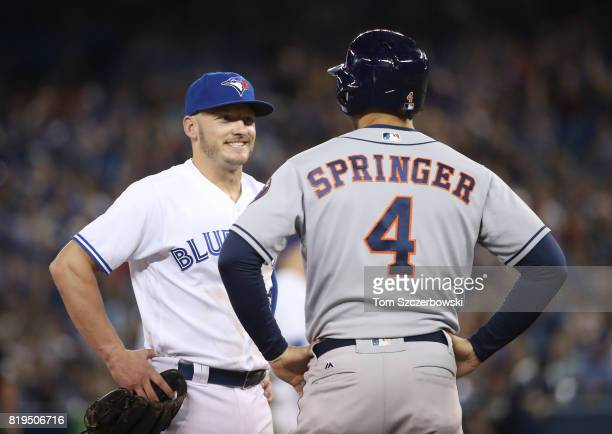 Josh Donaldson of the Toronto Blue Jays talks to George Springer of the Houston Astros as he stands on third base in the first inning during MLB game...