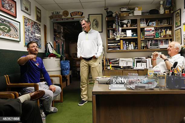 Josh Donaldson of the Toronto Blue Jays talks with General Manager Billy Beane and Equipment Manager Steve Vucinich in the Athletics clubhouse prior...