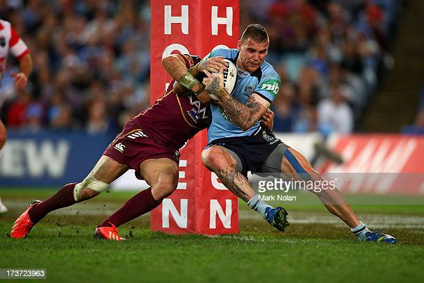 Josh Dugan of the Blues is tackled by Billy Slater of the Maroons during game three of the ARL State of Origin series between the New South Wales...
