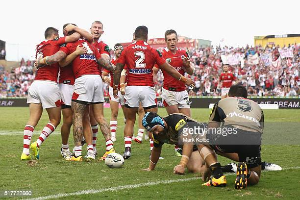 Josh Dugan of the Dragons celebrates with his team mates after scoring a try as Jamie Soward and Dallin WateneZelezniak of the Panthers look dejected...