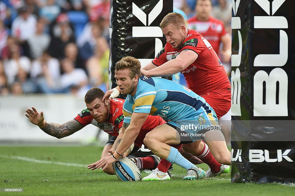 Josh Dugan of the Dragons grounds the ball ahead of Kane Elgey of the Titans during the round 25 NRL match between the Gold Coast Titans and the St...
