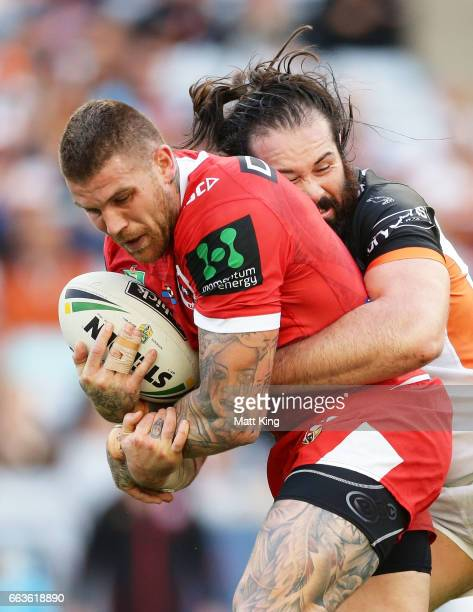 Josh Dugan of the Dragons is tackled by Aaron Woods of the Tigers during the round five NRL match between the Wests Tigers and the St George...