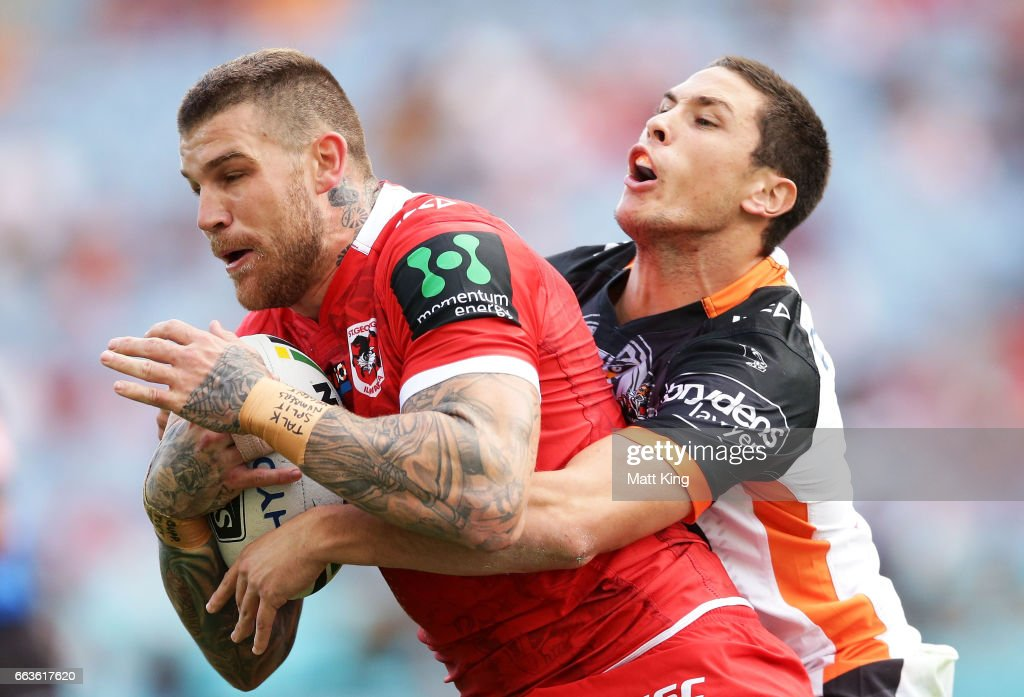 Josh Dugan of the Dragons is tackled by Mitchell Moses of the Tigers during the round five NRL match between the Wests Tigers and the St George Illawarra Dragons at ANZ Stadium on April 2, 2017 in Sydney, Australia.