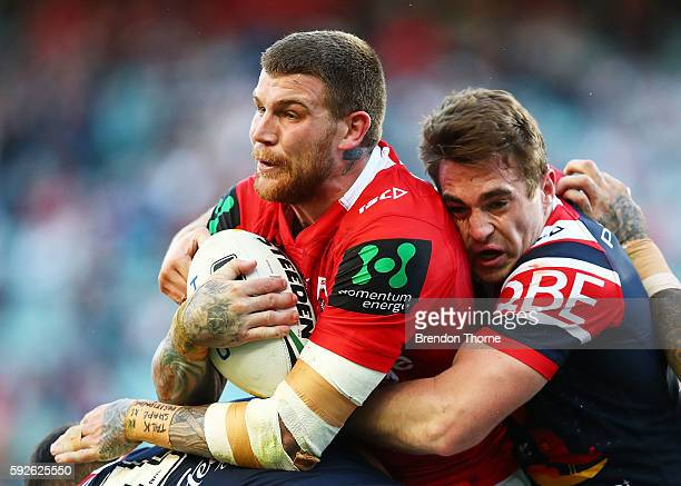 Josh Dugan of the Dragons is tackled by Roosters defence during the round 24 NRL match between the Sydney Roosters and the St George Illawarra...