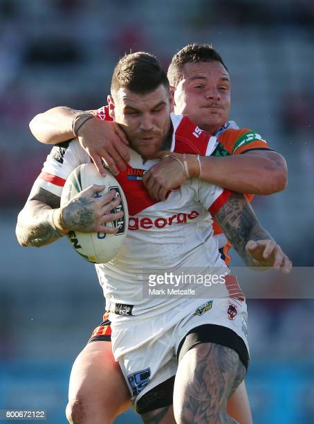 Josh Dugan of the Dragons is tackled during the round 16 NRL match between the St George Illawarra Dragons and the Newcastle Knights at UOW Jubilee...