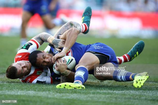 Josh Dugan of the Dragons tackles Will Hopoate of the Bulldogs during the round 26 NRL match between the St George Illawarra Dragons and the...