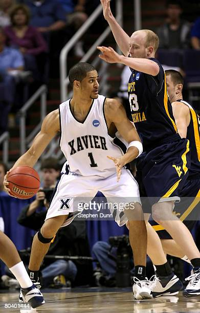 Josh Duncan of the Xavier Musketeers controls the ball against Jamie Smalligan of the West Virginia Mountaineers during the second half of the West...