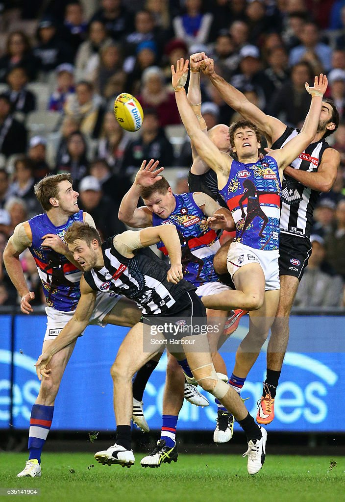 Josh Dunkley of the Bulldogs and Brodie Grundy of the Magpies and Ben Reid of the Magpies compete for the ball during the round 10 AFL match between the Collingwood Magpies and the Western Bulldogs at Melbourne Cricket Ground on May 29, 2016 in Melbourne, Australia.