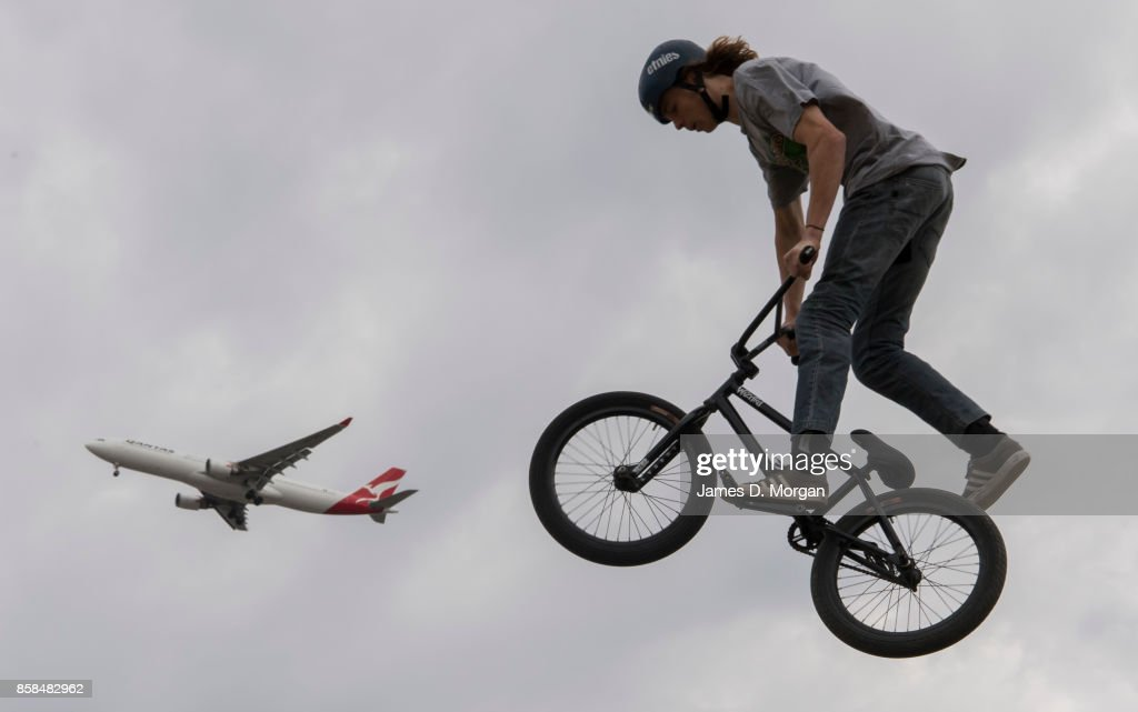 Josh Eaton, a BMX bicycle freestyle athlete chases a Qantas Airbus A330 aircraft on October 7, 2017 in Sydney, Australia. The Big Adventure at Sydney Park is part of the month-long Sydney Rides Festival, aimed at encouraging Sydney residents to get outdoors and active.