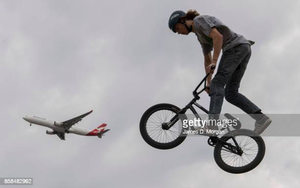 Josh Eaton a BMX bicycle freestyle athlete chases a Qantas Airbus A330 aircraft on October 7 2017 in Sydney Australia The Big Adventure at Sydney...