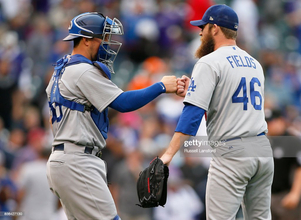 Josh Fields #46 and Kyle Farmer #65 of the Los Angeles Dodgers celebrate a win over the Colorado Rockies at Coors Field on October 1, 2017 in Denver, Colorado.