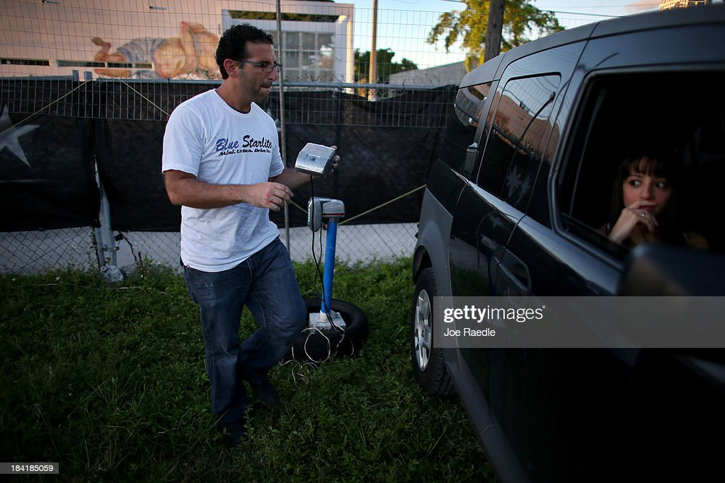 Josh Frank carries a window speaker to a vehicle as he prepares to show 'Back to the Future' at The Blue Starlite Mini Urban Drive-In that he created on October 11, 2013 in Miami, Florida. Many traditional drive-in theaters around the United States have closed but the owner of The Blue Starlite held a grand opening for his small outdoor facility, which can accommodate 20 to 24 cars and has seats near the front of the viewing area, with hopes it will become popular in the urban core of Miami.