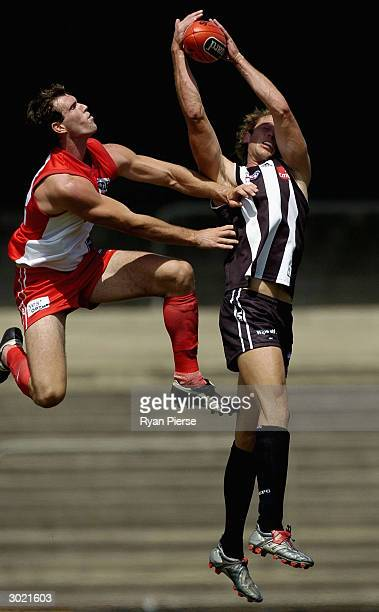 Josh Fraser for the Magpies marks despite pressure from James Meiklejohn for the Swans during the AFL Trial match between the Collingwood Magpies and...