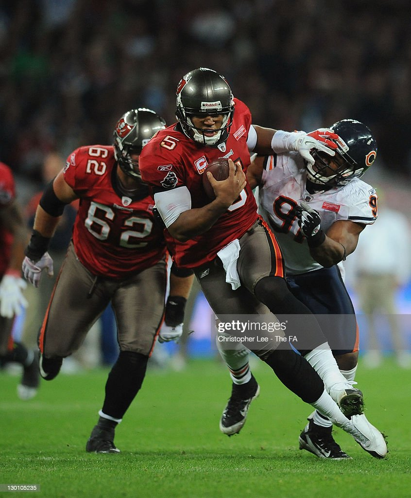 <a gi-track='captionPersonalityLinkClicked' href=/galleries/search?phrase=Josh+Freeman&family=editorial&specificpeople=4036797 ng-click='$event.stopPropagation()'>Josh Freeman</a> #5 of the Tampa Bay Buccaneers evades the tackle of <a gi-track='captionPersonalityLinkClicked' href=/galleries/search?phrase=Amobi+Okoye&family=editorial&specificpeople=2285401 ng-click='$event.stopPropagation()'>Amobi Okoye</a> #91 of the Chicago Bears during the NFL International Series match between Chicago Bears and Tampa Bay Buccaneers at Wembley Stadium on October 23, 2011 in London, England. This is the fifth occasion where a regular season NFL match has been played in London.