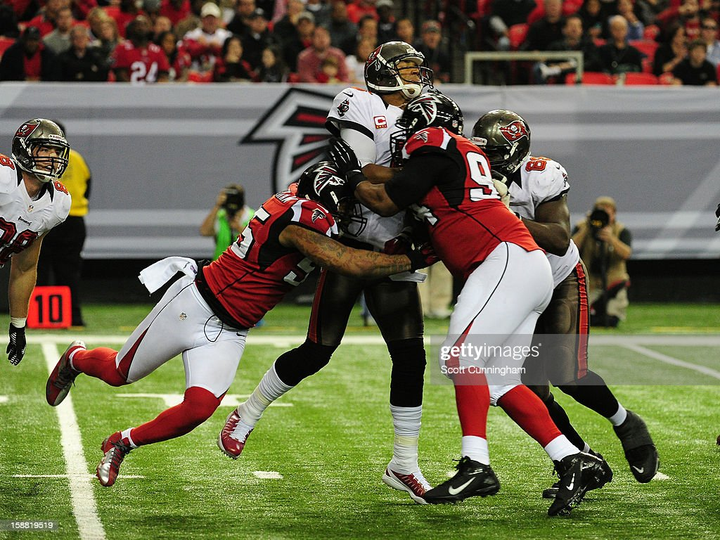 <a gi-track='captionPersonalityLinkClicked' href=/galleries/search?phrase=Josh+Freeman&family=editorial&specificpeople=4036797 ng-click='$event.stopPropagation()'>Josh Freeman</a> #5 of the Tampa Bay Buccaneers is hit by Peria Jerry #94 and John Abraham #55 of the Atlanta Falcons at the Georgia Dome on December 30, 2012 in Atlanta, Georgia
