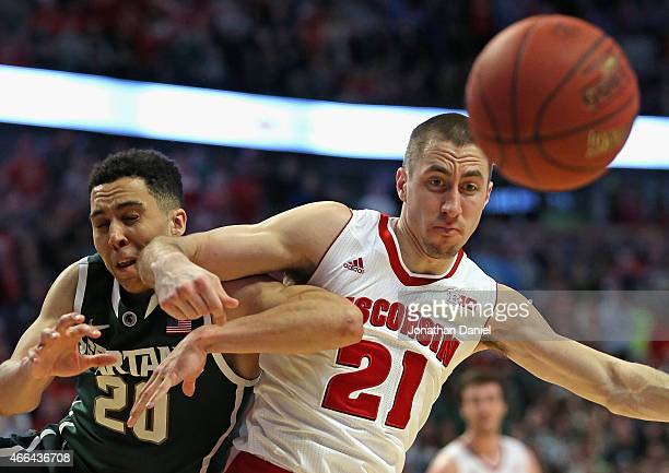Josh Gasser of the Wisconsin Badgers throws an elbow into Travis Trice of the Michigan State Spartans as they chase loose ball during the...