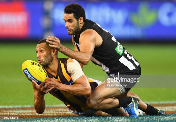 Josh Gibson of the Hawks handballs whilst being tackled by Daniel Wells of the Magpies during the round nine AFL match between the Collingwood...