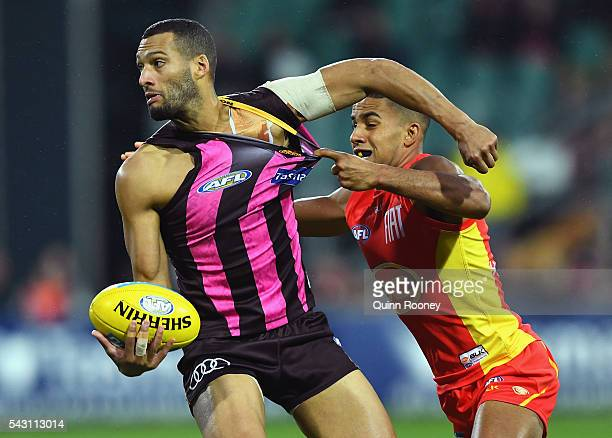 Josh Gibson of the Hawks handballs whilst being tackled by Touk Miller of the Suns during the round 14 AFL match between the Hawthorn Hawks and the...