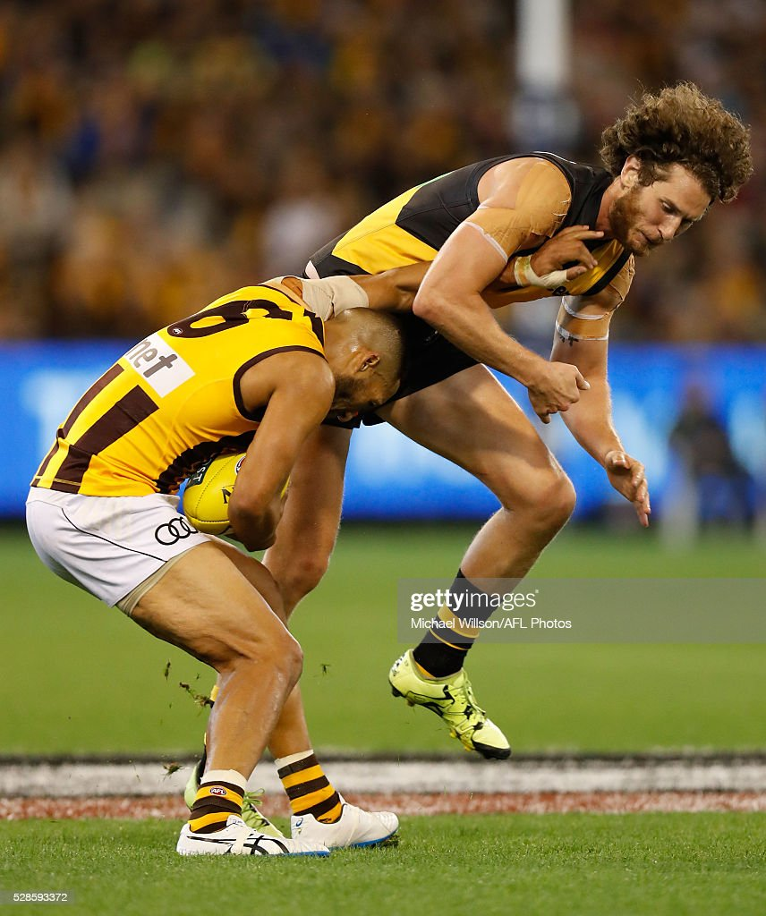 Josh Gibson of the Hawks is tackled by Ty Vickery of the Tigers during the 2016 AFL Round 07 match between the Richmond Tigers and the Hawthorn Hawks at the Melbourne Cricket Ground, Melbourne on May 6, 2016.