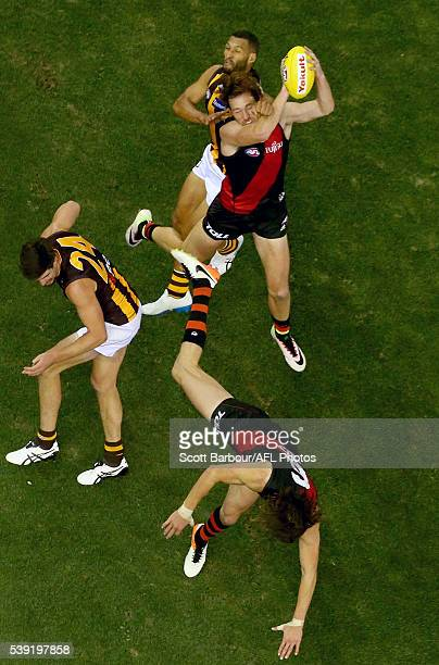 Josh Gibson of the Hawks Mitch Brown of the Bombers and Joe Daniher of the Bombers compete for the ball during the round 12 AFL match between the...