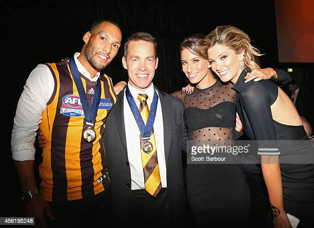 Josh Gibson of the Hawks poses with his girlfriend Renee Bargh Delta Goodrem and Hawks coach Alastair Clarkson as they attend the Hawthorn Hawks AFL...