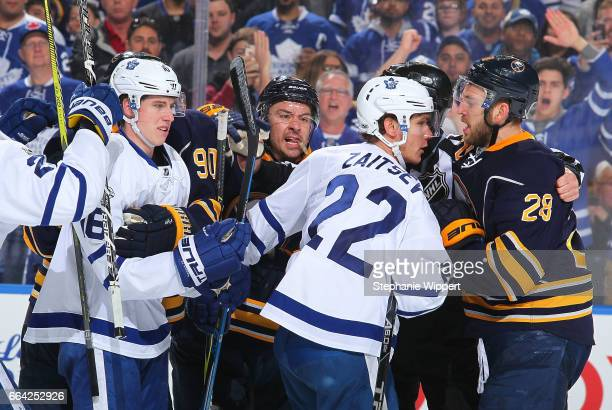 Josh Gorges and Zemgus Girgensons of the Buffalo Sabres battle with Nikita Zaitsev of the Toronto Maple Leafs during an NHL game at the KeyBank...