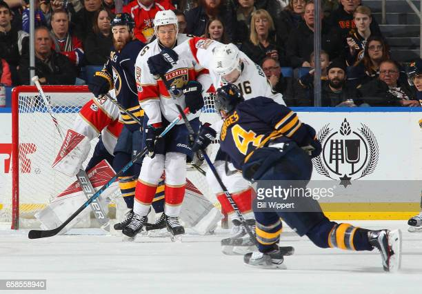 Josh Gorges of the Buffalo Sabres fires a second period shot against Aleksander Barkov and Alex Petrovic of the Florida Panthers during an NHL game...