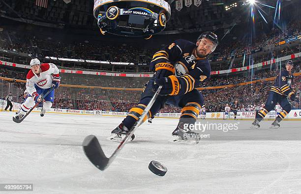 Josh Gorges of the Buffalo Sabres reaches for the puck ahead of Brendan Gallagher of the Montreal Canadiens during an NHL game on October 23 2015 at...