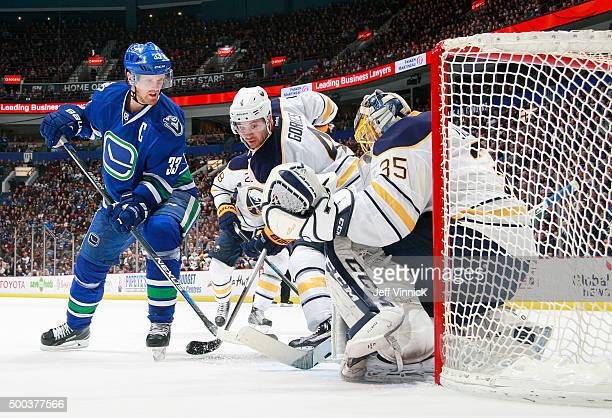 Josh Gorges of the Buffalo Sabres watches as Henrik Sedin of the Vancouver Canucks deflects the puck behind Linus Ullmark of the Sabres for a goal...