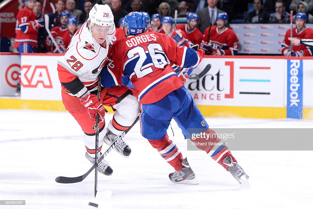 <a gi-track='captionPersonalityLinkClicked' href=/galleries/search?phrase=Josh+Gorges&family=editorial&specificpeople=550446 ng-click='$event.stopPropagation()'>Josh Gorges</a> #26 of the Montreal Canadiens body checks <a gi-track='captionPersonalityLinkClicked' href=/galleries/search?phrase=Alexander+Semin&family=editorial&specificpeople=206654 ng-click='$event.stopPropagation()'>Alexander Semin</a> #28 of the Carolina Hurricanes during the NHL game at the Bell Centre on February 18, 2013 in Montreal, Quebec, Canada. The Canadiens defeated the Hurricanes 3-0.