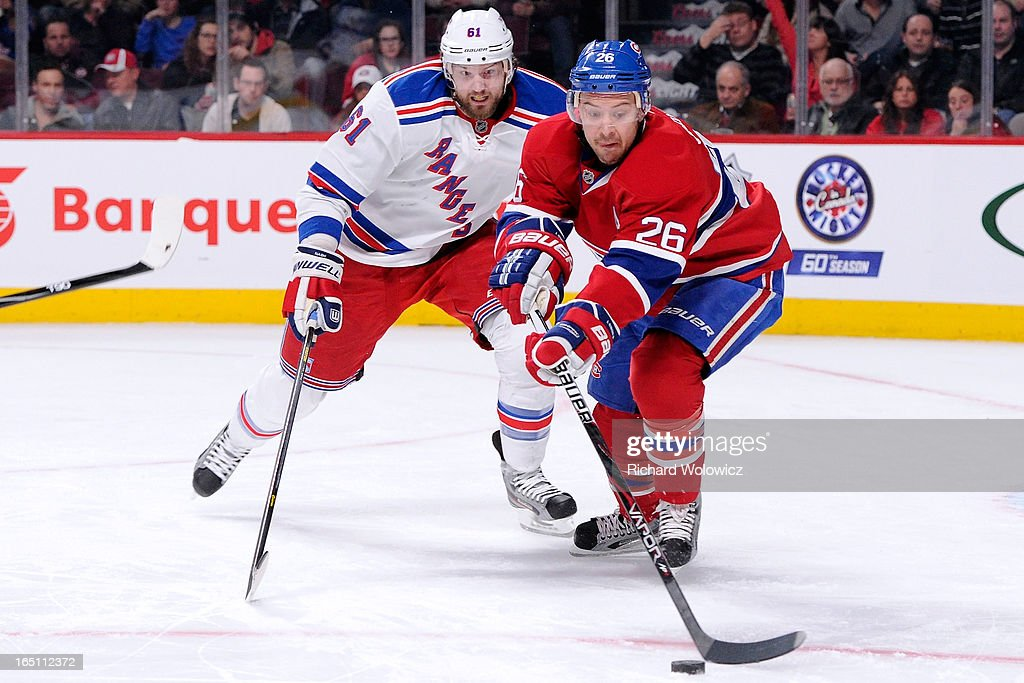 Josh Gorges #26 of the Montreal Canadiens clears the puck front of Rick Nash #61 of the New York Rangers during the NHL game at the Bell Centre on March 30, 2013 in Montreal, Quebec, Canada.